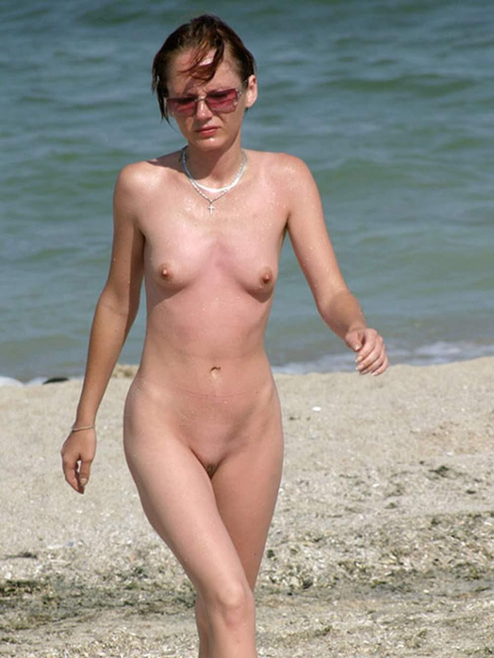 Young nudist takes a stroll in the sand