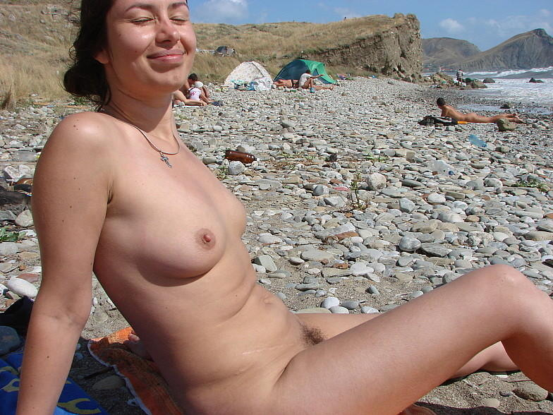 Lascivious milf smiles on flashing camera while sunbathing