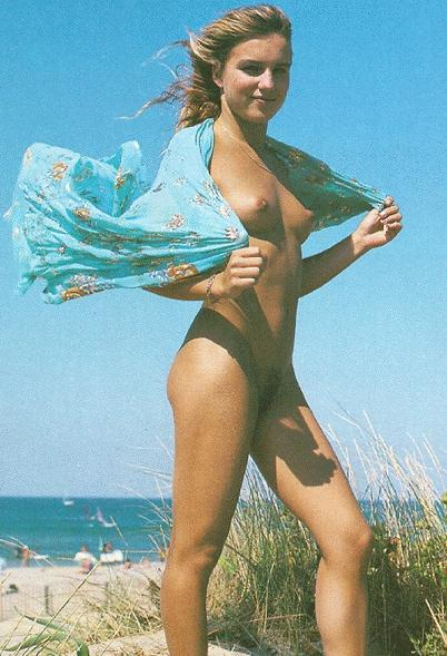 Nude blonde chick poses in front of the camera with just a blue scarf for cover
