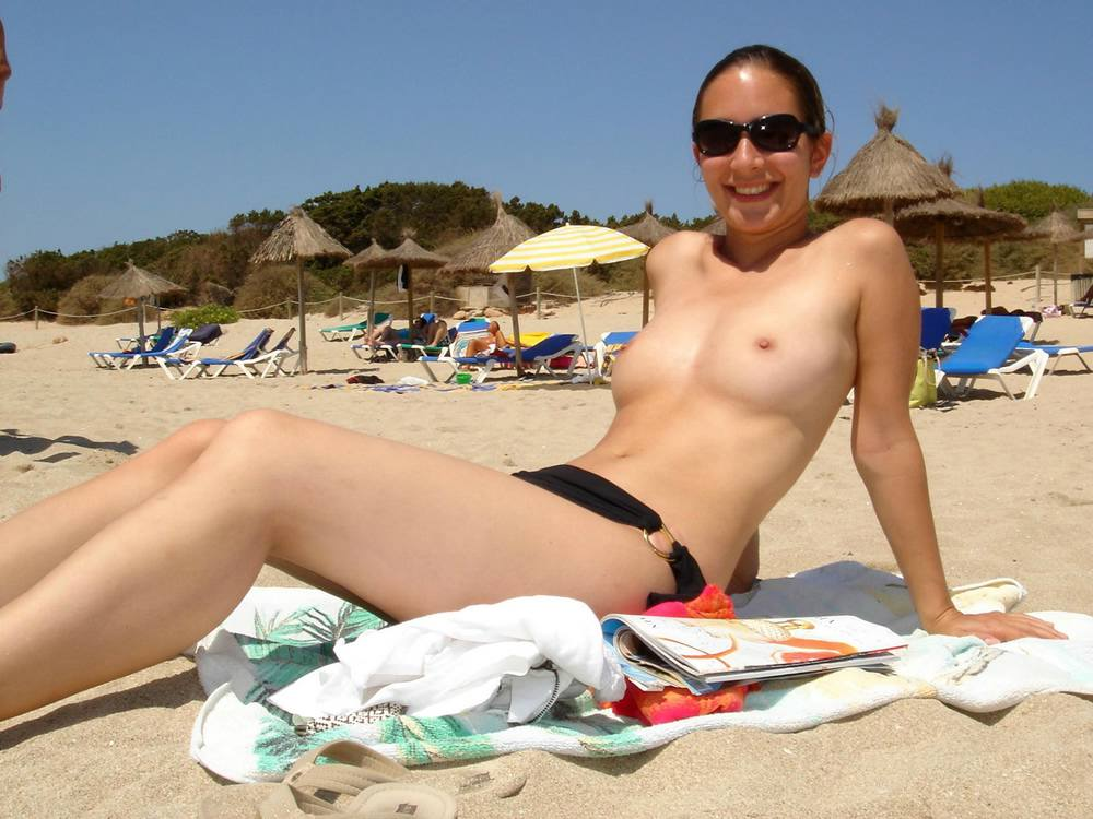Pretty pale nudist smiles for hot portrait shots in the sand