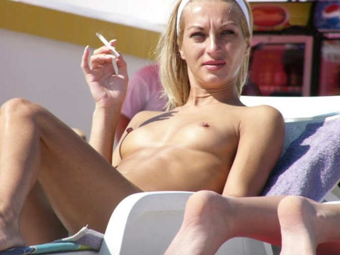 Stunning nude blonde enjoys a quick cigarette break