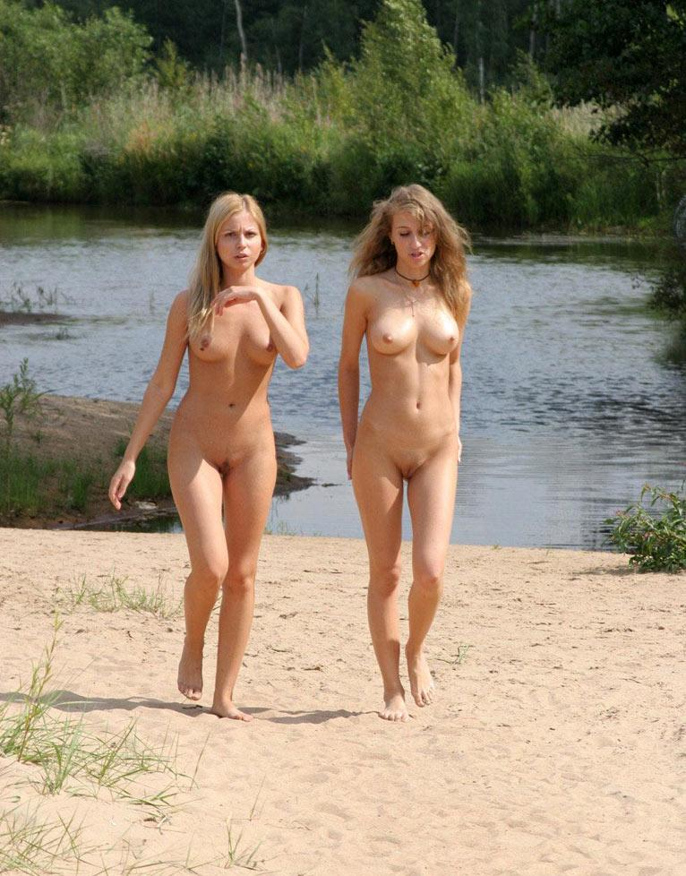 Young naked damsels promenade along the sandy beach of a lagoon