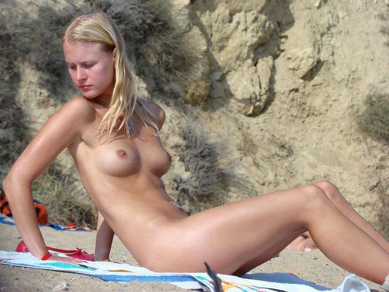 Young nudist preps her mat before lying down