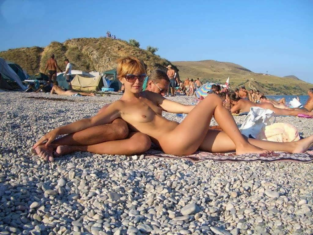 Nudist couple about to bump bellies on the beach