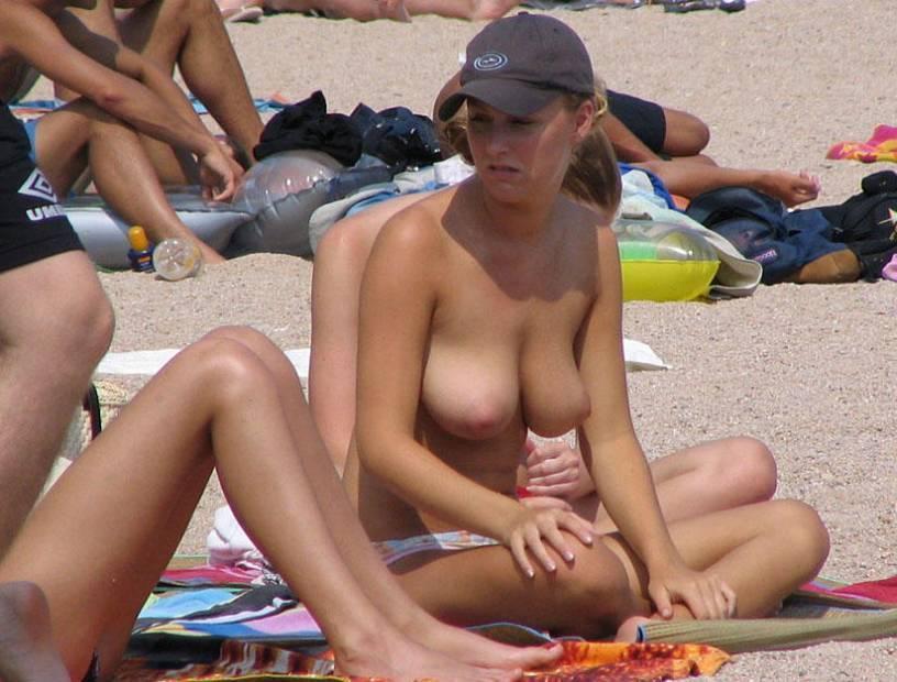 Pretty topless maiden unwary of lurking beach voyeurs