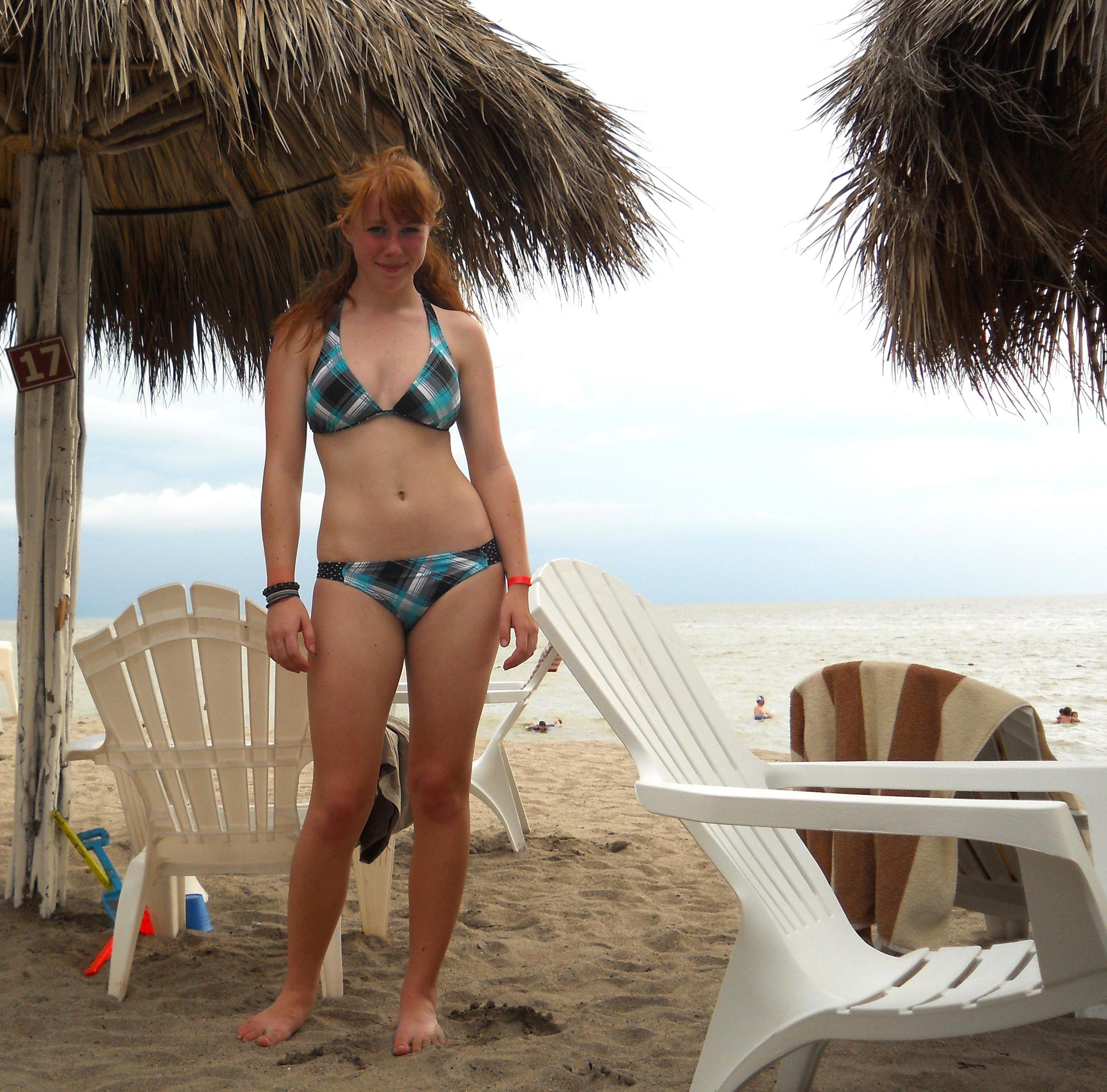 Provocative redhead under the parasol in bikinis