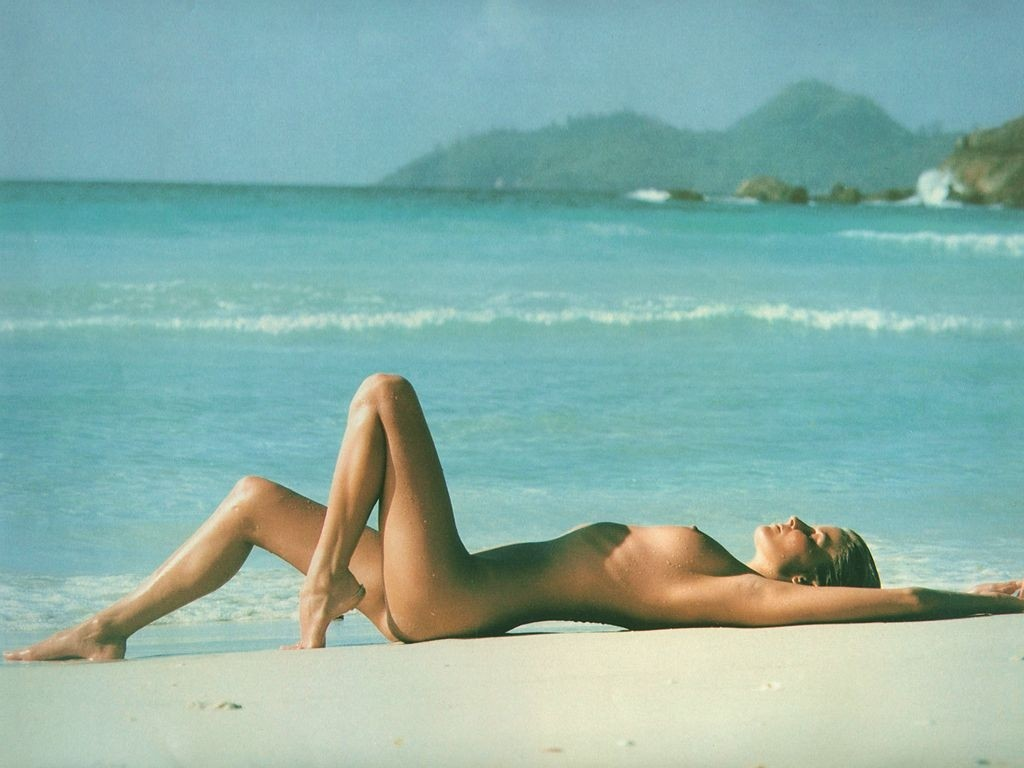 She is looking hot as hell wearing nothing and posing on the sand beach