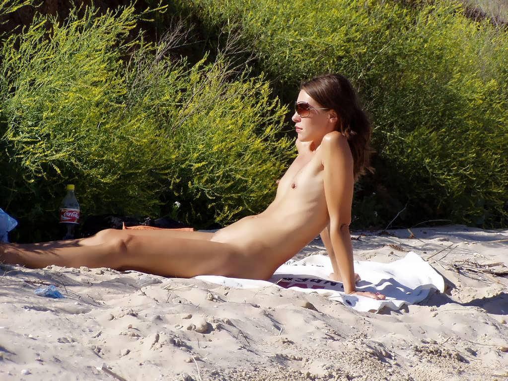 Sunbathing pretty naked chick behind the bush