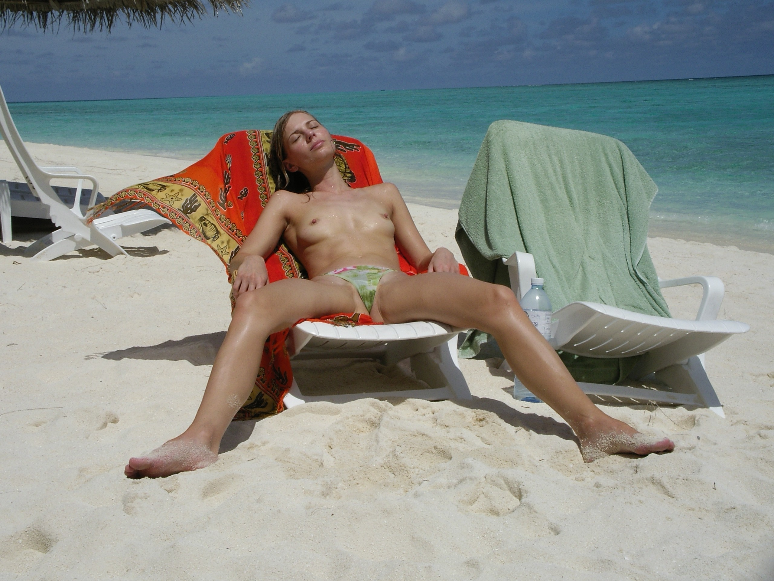 Taking a rest on the beach and sunbathing only in panties