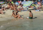 Two teens flirting with a lucky guy sitting in the sea