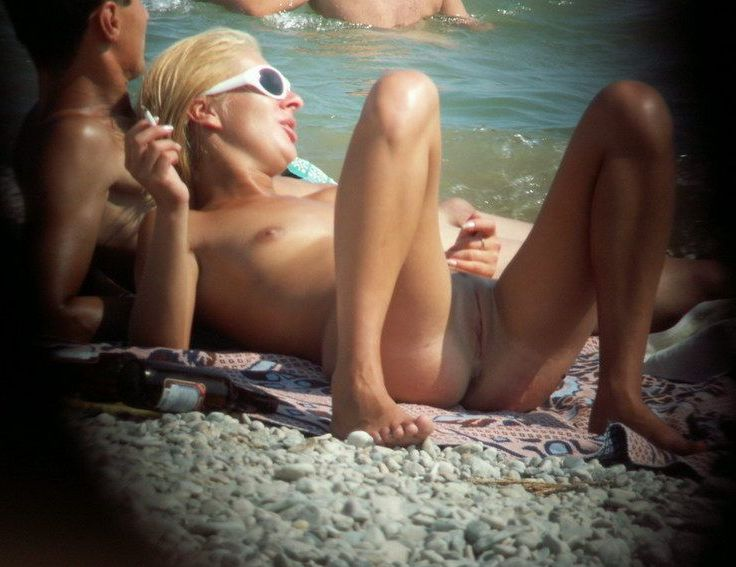 Blonde relaxing with a cigarette and spread legs