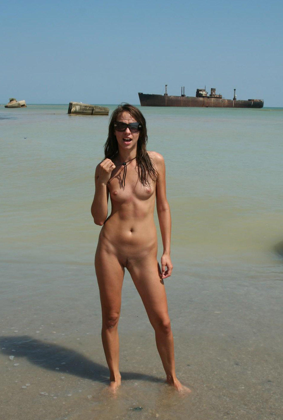 Chick with sunglasses standing in the water