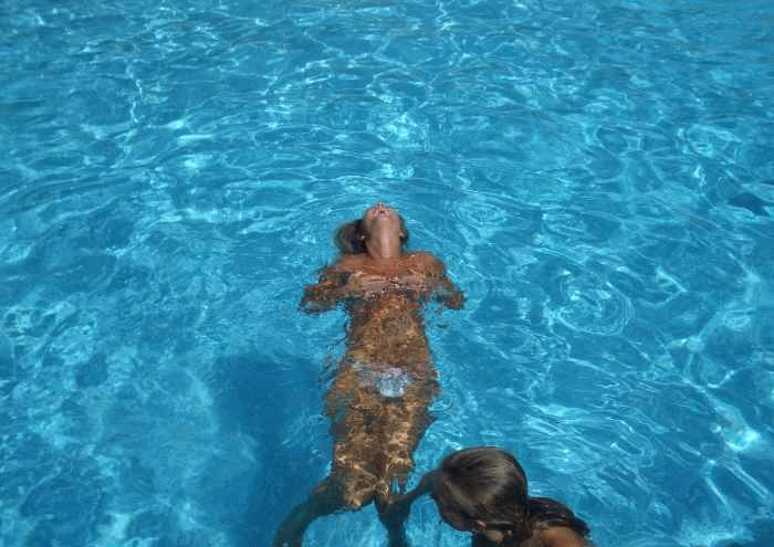 Naked beauty swimming topless in the pool