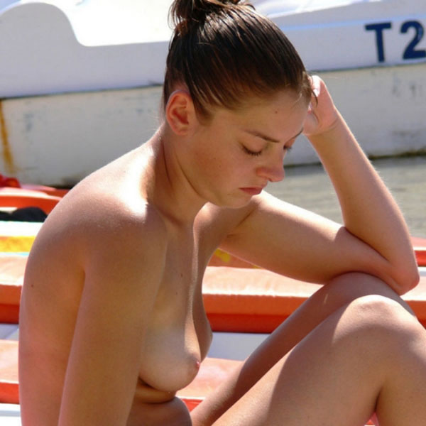Sad woman topless on beach