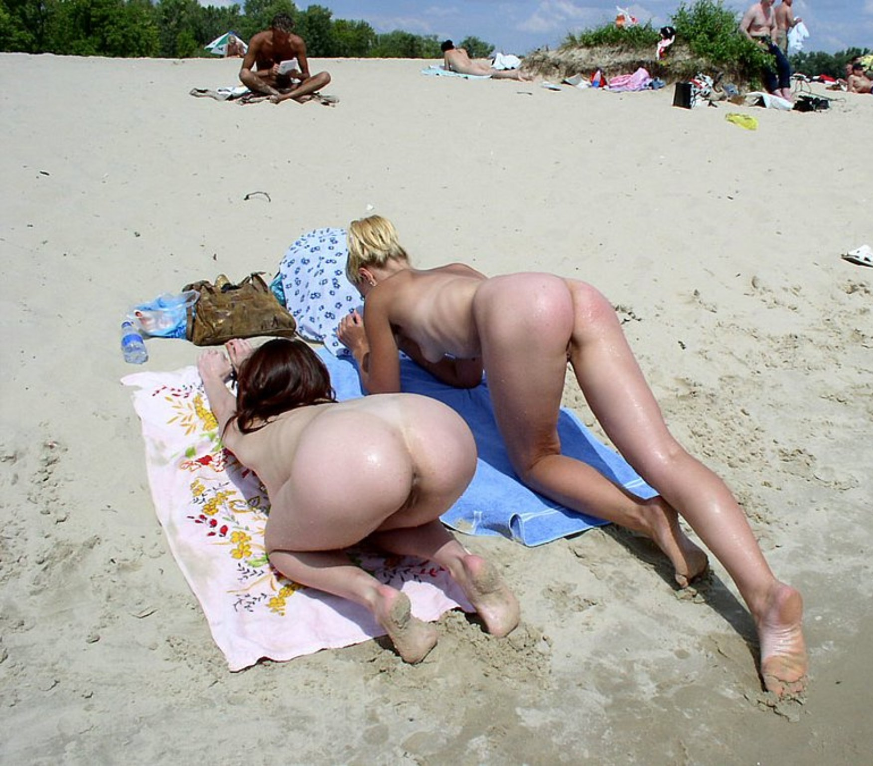 Two girls doggy style on a beach towel