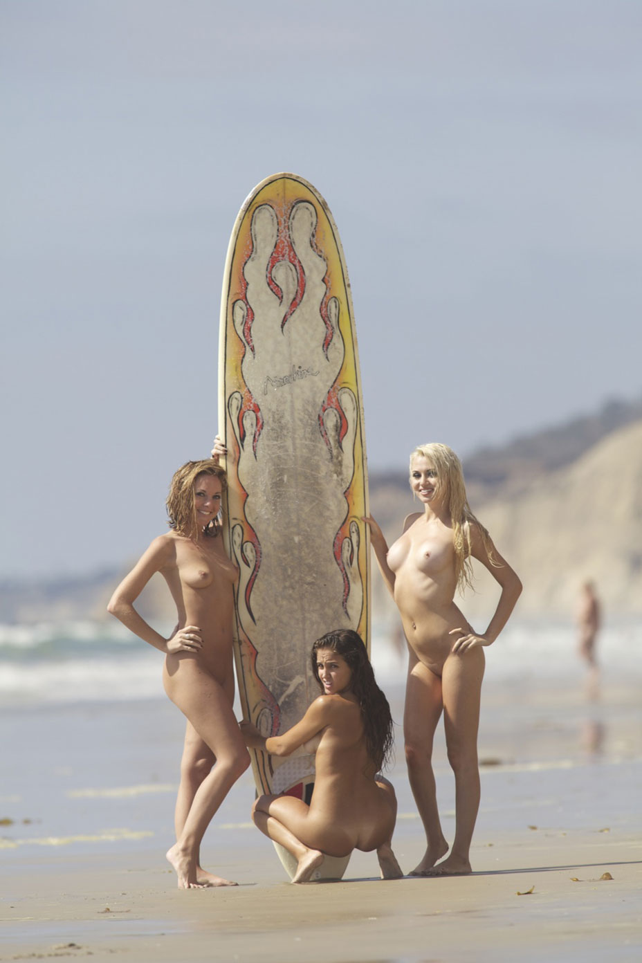 Hot babes posing nude with a huge surfing board