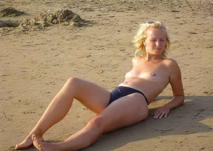 Topless blonde babe laying on the sand