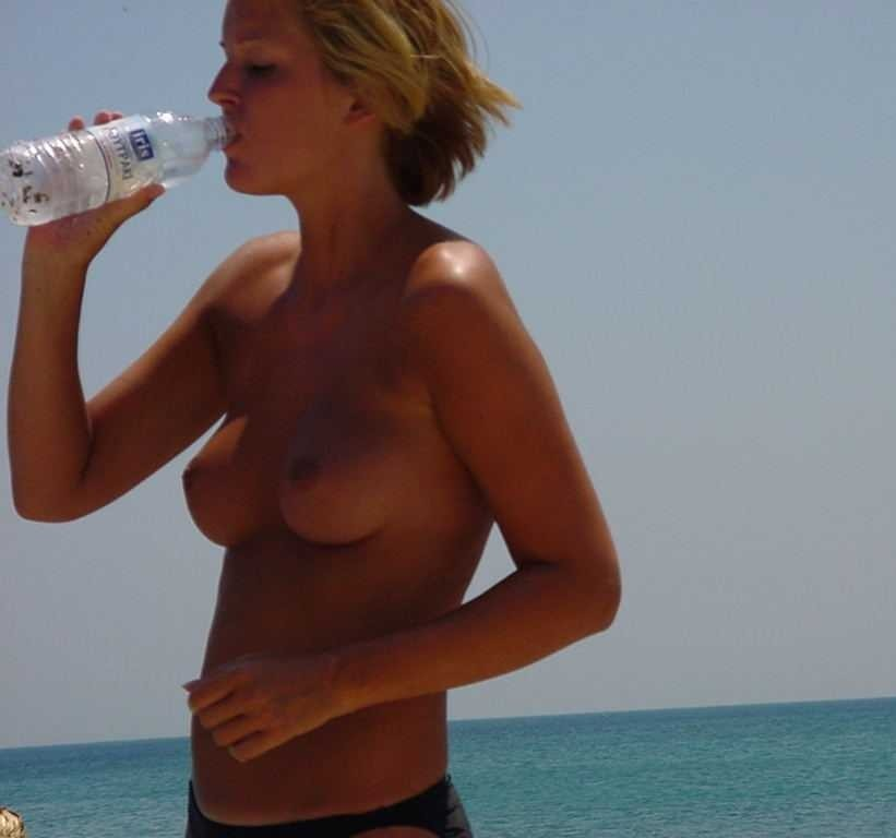 Topless hot babe is a bit thirsty after a day at beach