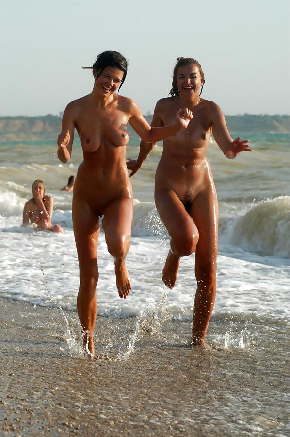 Two hot naked friends taking a playful jog through the surf